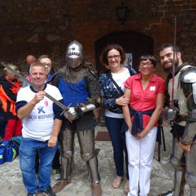 uśmiechnięci członkowie kręgów wsparcia i osoby z NI podczas dni Nidzicy zdjęcie z rycerzami