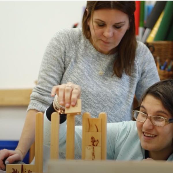 osoba z niepełnospranością intelektualną ze swoim terapeutom układają klocki