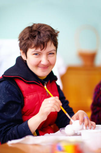 young adult woman with disability engaged in craftsmanship in rehabilitation center